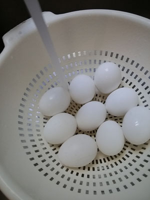 Place hard-boiled eggs in colander and rinse with cold water